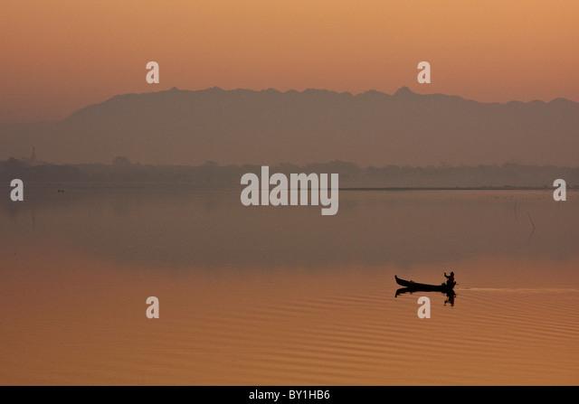 Myanmar, Burma, Amarapura. A fisherman paddling across Taungthaman Lake at sunrise, Amarapura. - Stock-Bilder