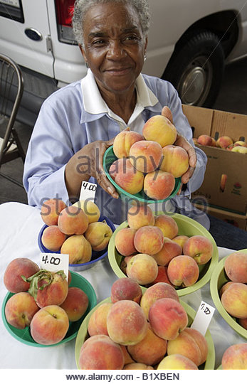 Little Rock Arkansas River Market Farmers Market locally grown produce buyers sellers Black woman peaches bowls - Stock Image