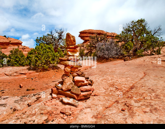 A trail-marking cairn of red rocks in Arches National Park, Utah, is a human-made pile of stones, often in conical - Stock Image