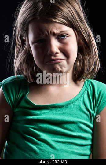 Low Key Shot of an Upset Young Girl against Black Background - Stock-Bilder