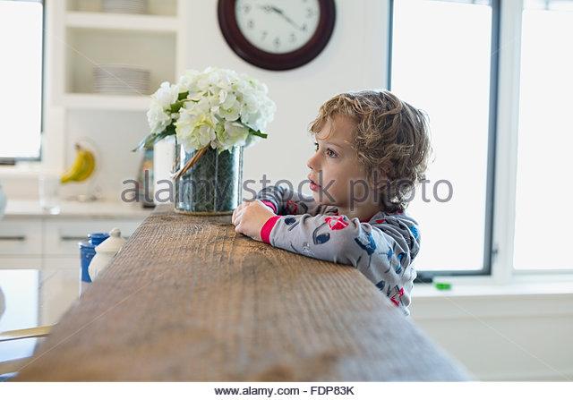 Boy in pajamas leaning on kitchen breakfast bar - Stock Image
