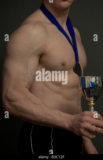 Side view of a man with trophy and medal - Stock Image