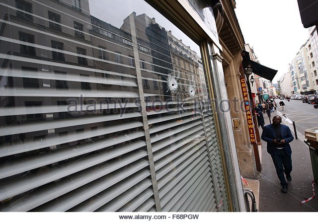 Paris, France. 14th November, 2015. A man looks a bullet hole that damaged a window of a patisserie on the rue de - Stock Image