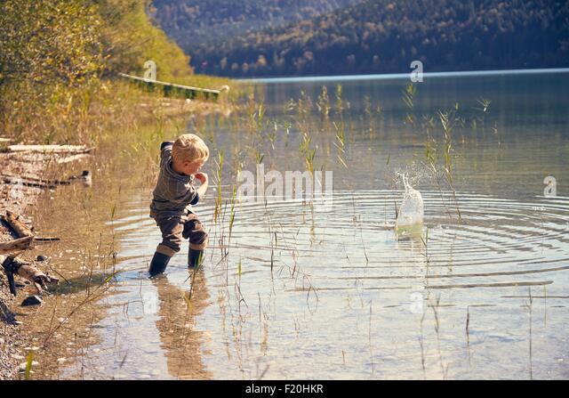Boy skimming stones in lake, Kochel, Bavaria, Germany - Stock Image