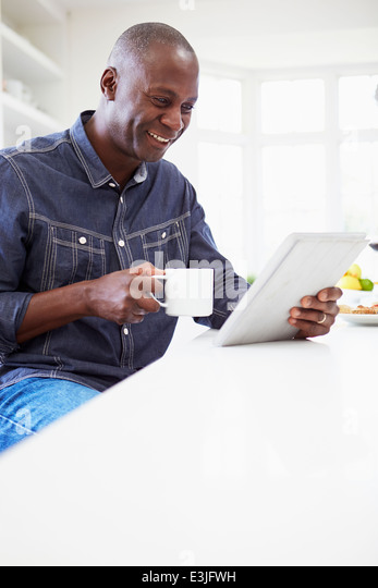 African American Man Using Digital Tablet At Home - Stock Image