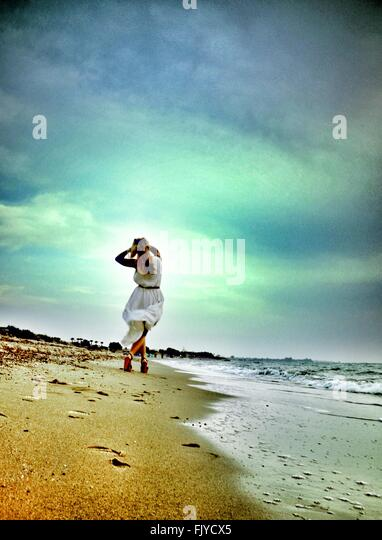 Low Angle View Of Young Woman Walking On Beach Against Cloudy Sky - Stock-Bilder