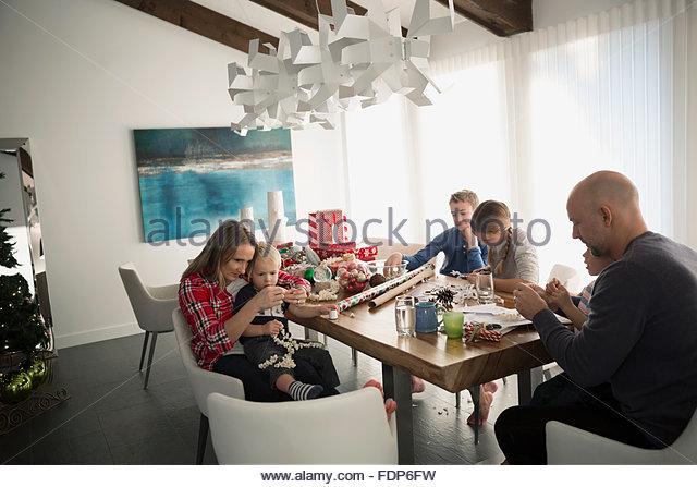Family wrapping Christmas gifts at dining table - Stock Image