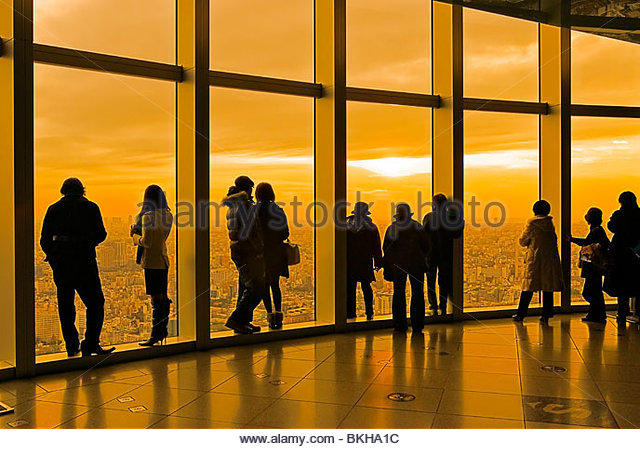 People looking at view from Mori Tower observation deck at sunset, Tokyo, Japan. - Stock Image