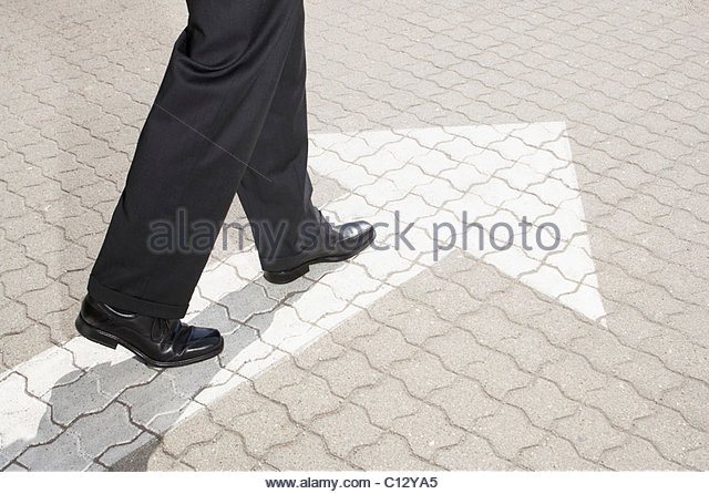 detail of business person walking on pavement with arrow - Stock Image
