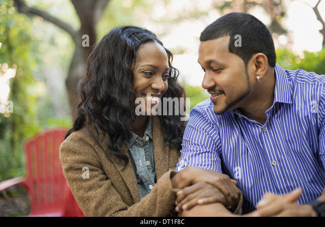 Scenes from urban life in New York City A man and a woman a couple with linked arms sitting side by side - Stock Image