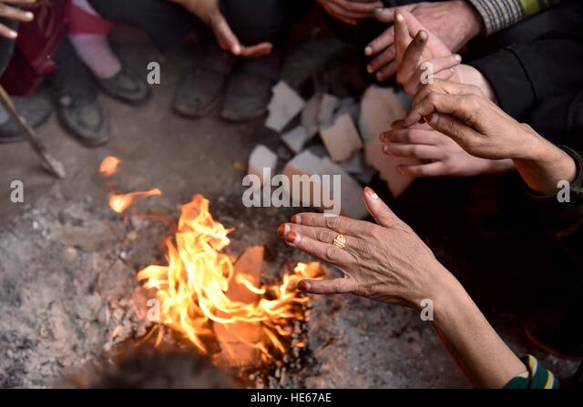 Aleppo, Syria. 18th Dec, 2016. Displaced Syrians make a fire to keep warm at the Jibreen temporary shelter, south - Stock-Bilder