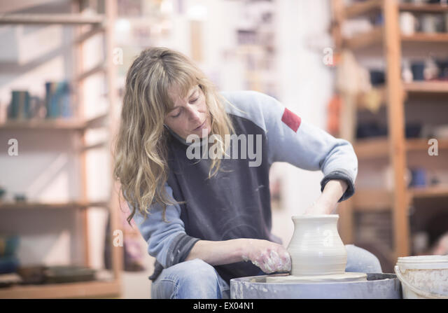 Female potter forming clay pot on pottery wheel in workshop - Stock Image