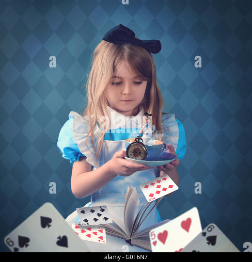 A little girl is holding a teacup with game cards and a book. The child is inside the cup for a surreal fairy tale - Stock Image
