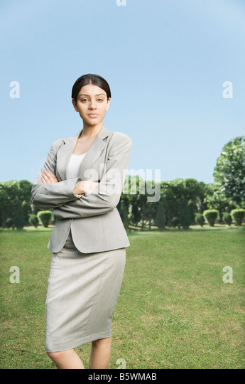 Businesswoman standing with her arms crossed - Stock-Bilder