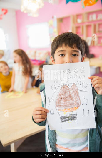 Student showing drawing in classroom - Stock Image