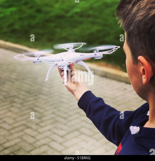 A young boy flying his drone in a rural area of Surrey. - Stock Image