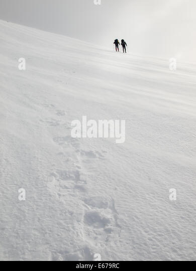 two men with heavy backpacks crossing a snowfield on snowshoes in  winter mountains with tracks in foreground - Stock Image