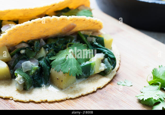 Two vegan soft tacos filled with potatoes and spinach and topped with cilantro. - Stock Image