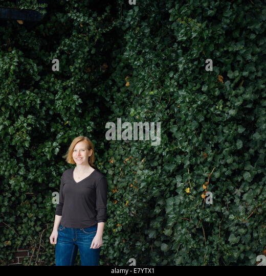 Woman standing against ivy foliage - Stock Image