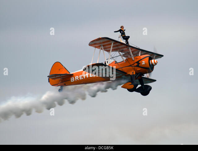 Eastbourne, East Sussex, UK. 16 August 2013. Breitling Wingwalkers perform breathtaking acrobatics on 1940s Boeing - Stock Image