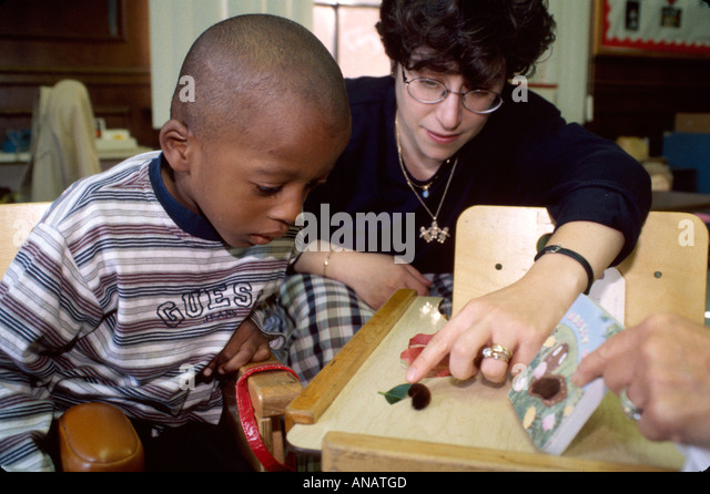 New Jersey East Orange Cerebral Palsy Center disabled student female therapist Black boy caterpillar - Stock Image