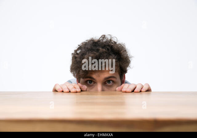 Young man with curly hair peeking from behind the desk - Stock Image