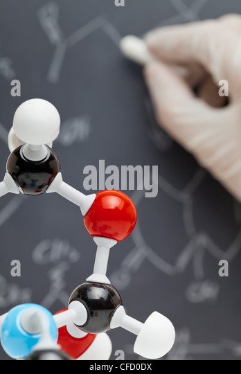 Molecule model with researcher writing on blackboard in the background - Stock Image