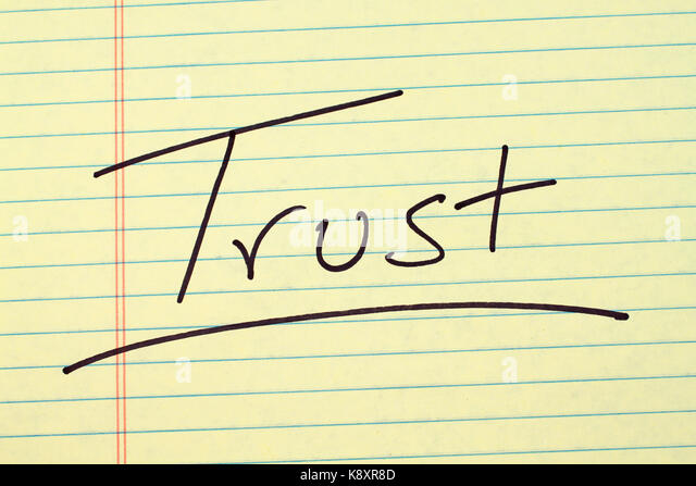 The word 'Trust' underlined on a yellow legal pad - Stock Image