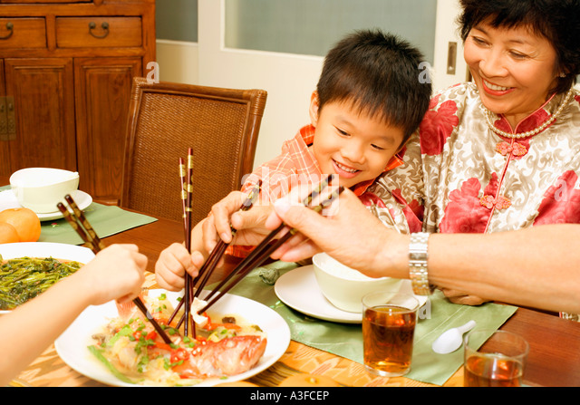 Mature woman and her grandson eating with chopsticks - Stock-Bilder