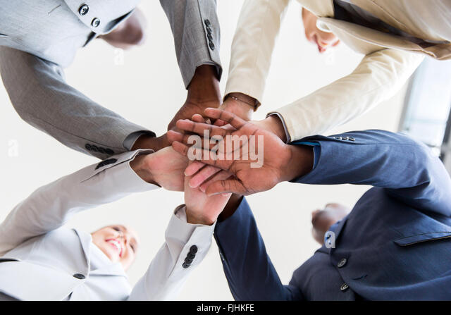 underneath view of business people hands together - Stock Image