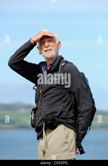 Rambler in Moelfre, Anglesey, North Wales surveys his surroundings. - Stock Image