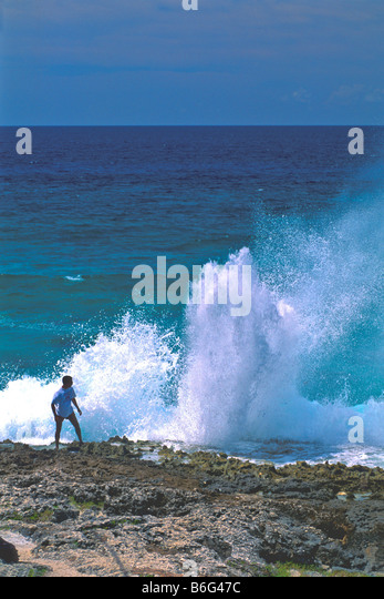 Blow Hole Grand Cayman Island man being covered in spray as blowhole explodes geyser like - Stock Image