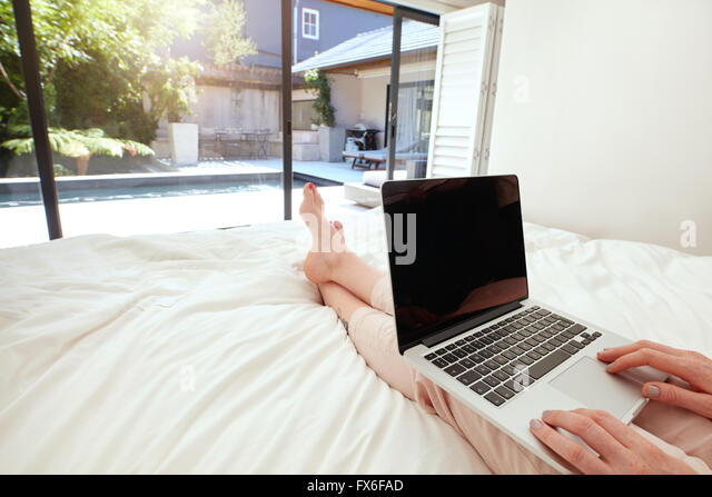 Closeup image of woman relaxing in bedroom and surfing internet on her laptop. Woman sitting on bed and working - Stock Image