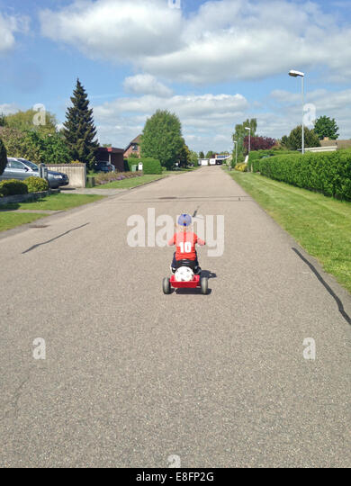 Rear view of a boy cycling along road on his tricycle, Denmark - Stock Image