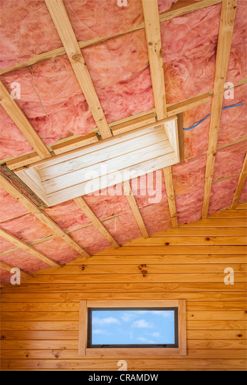 Fibreglass insulation installed in the sloping ceiling of a timber house. - Stock-Bilder