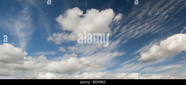 Altocumulus undulatus and cumulus clouds - Stock Image