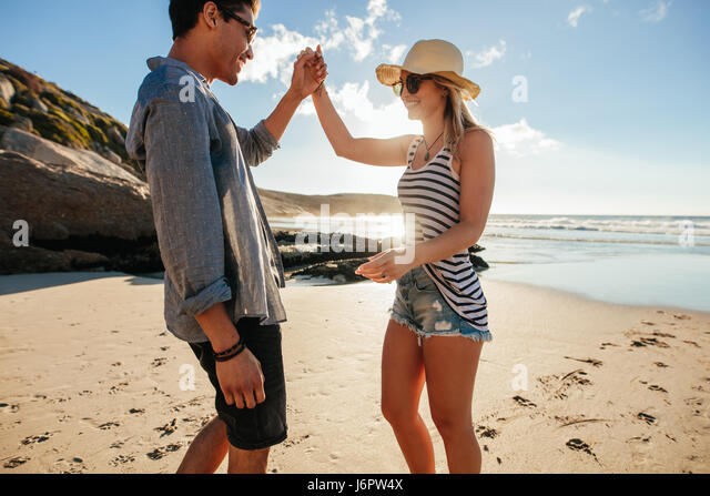 Shot of young man and woman dancing on the beach on a summer day. Romantic young couple dancing on the beach. - Stock Image