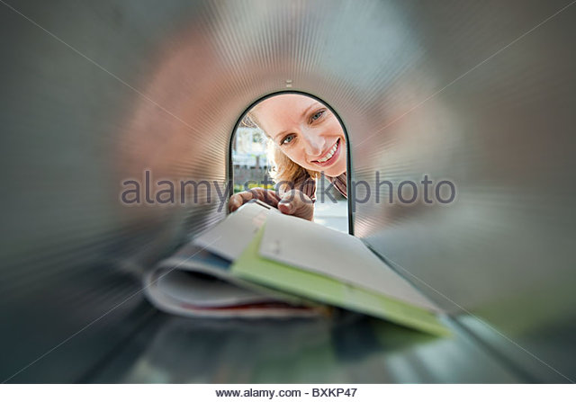 Woman collecting mail from mailbox - Stock Image