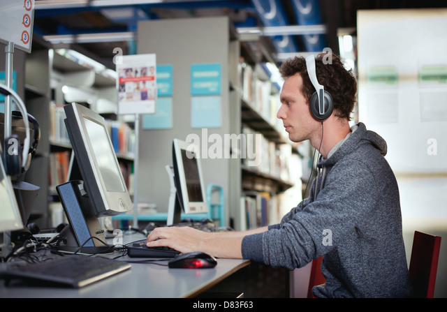 education, student working at the computer in the library - Stock Image