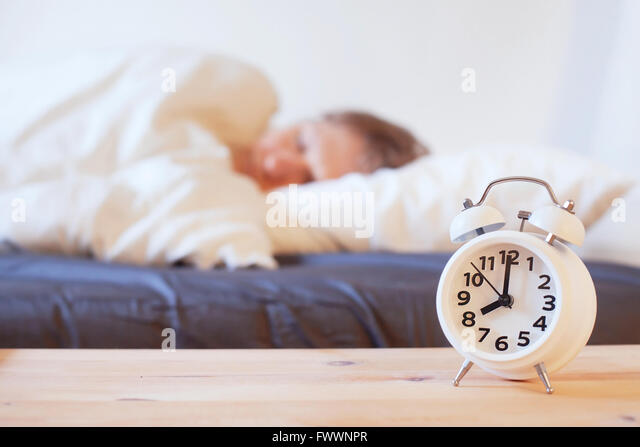 wake up in the morning with alarm clock, person sleeping in the bed - Stock-Bilder