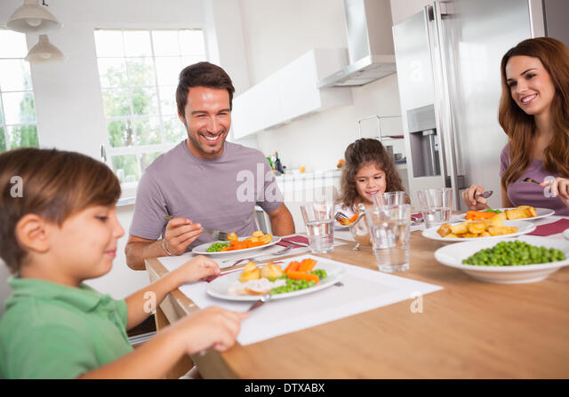 Family smiling around a good meal - Stock Image