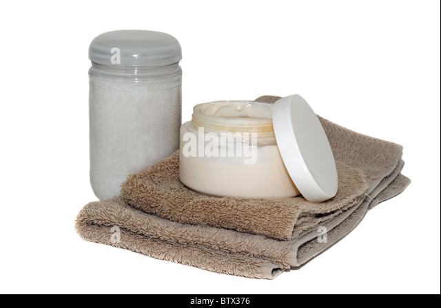 An open jar of facial cream and a bottle of bath beads with a wash rag and hand towel. - Stock Image