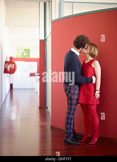 Mid adult couple kissing in corridor - Stock-Bilder