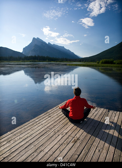 54 year old male meditating on dock at Vermillion Lake, Banff, Alberta, Canada. - Stock Image