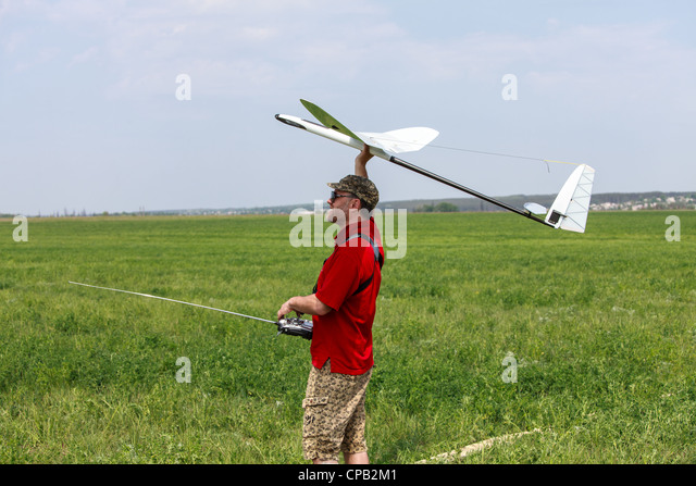 Man launches into the blue sky RC glider - Stock Image
