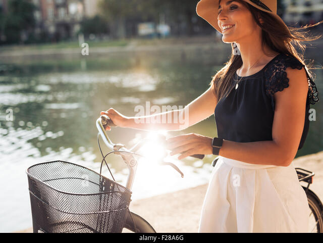 Cheerful young female at the park with her bicycle. Female model wearing hat looking away smiling while walking - Stock Image