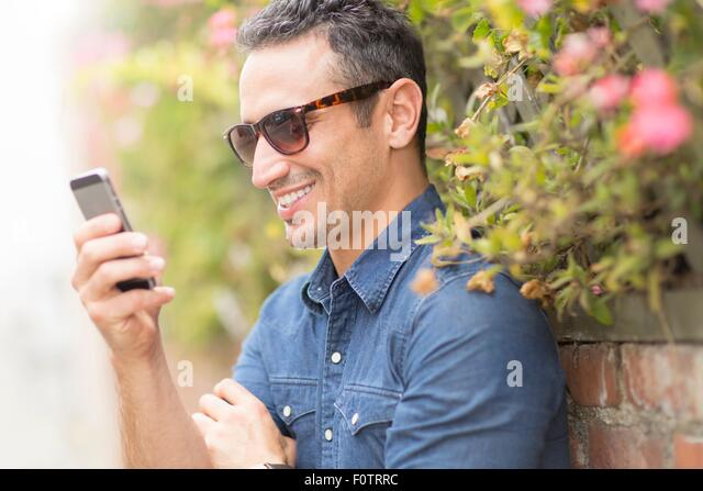 Mid adult man, outdoors, using mobile phone - Stock Image