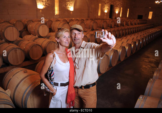 Tourism-Couple visiting a castle photographing in a barrel cellar in Bordeaux vineyard - Stock Image