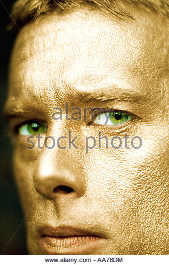Close up of a man with a metallic gold painted face and piercing green eyes. Focused Stare Staring - Stock Image