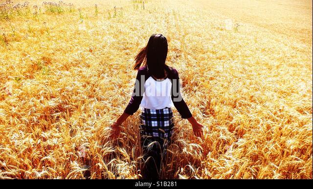 Girl walking in bright sunny wheat field - Stock Image